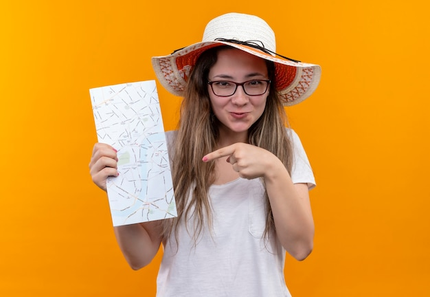 Young traveler woman in white t-shirt wearing summer hat holding map pointing with finger to it smiling with happy face standing over orange wall