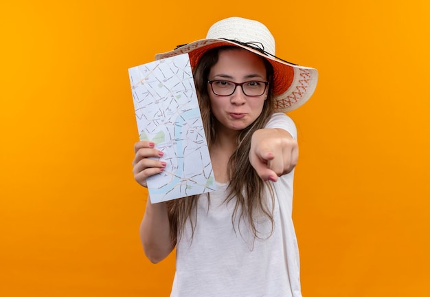 Giovane donna del viaggiatore in maglietta bianca che indossa cappello estivo che tiene la mappa che indica con il dito indice nella parte anteriore