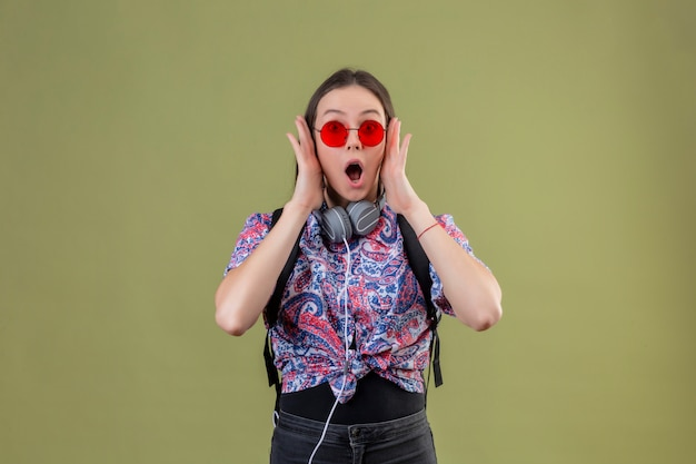 Young traveler woman with backpack and headphones wearing red sunglasses shocked standing with wide open mouth touching face with hands over green wall