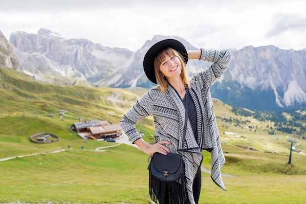 Young traveler woman with hat and backpack enjoying amazing mountain view