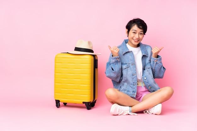 Молодой путешественник женщина с чемоданом, сидя на полу над изолированных розовый с недурно жест и улыбается