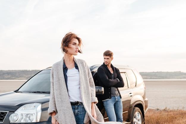 Пара молодых путешественников, стоя возле машины на открытом воздухе на поле