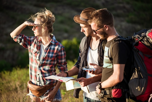 Young travelers looking for route on map, walking in canyon