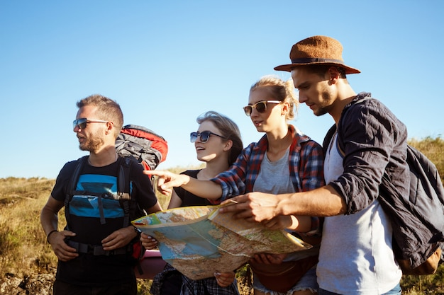 地図でルートを探して笑顔のバックパックを持つ若い旅行者
