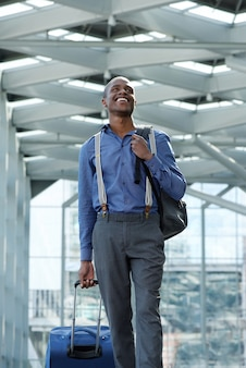 Young traveling businessman walking with suitcase