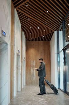 Young traveling businessman with suitcase using smartphone while waiting for elevator in long corridor of hotel