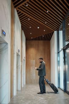 Молодой путешествующий бизнесмен с чемоданом, используя смартфон, ожидая лифта в длинном коридоре отеля