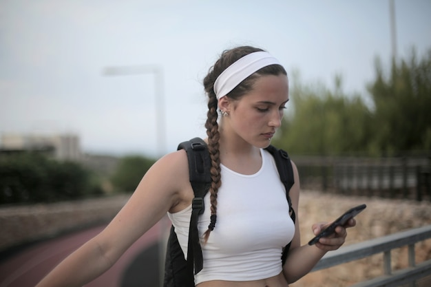 お下げと彼女の携帯電話を見てバックパックを持つ若い旅行少女