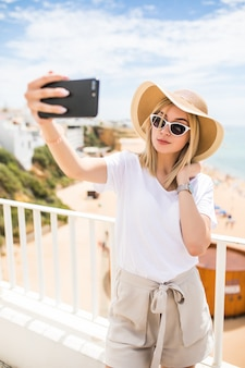Young traveling woman holding phone making selfie against sea