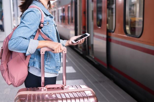 Молодая девушка путешественника в джинсовой куртке с концепцией смарт-телефона, розовой сумки и багажа ждать поезда на платформе, космосе экземпляра, концепции перемещения или перевозки