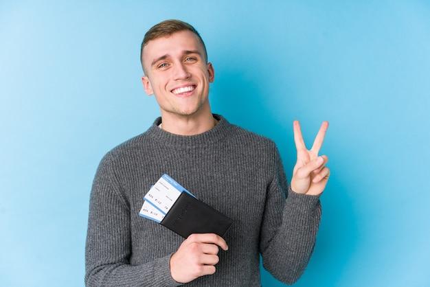 搭乗券を持っている若い旅行者の男性は、指で平和のシンボルを示して楽しくてのんきです。