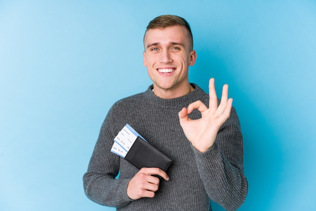 Young traveller man holding a boarding pass cheerful and confident showing ok gesture.
