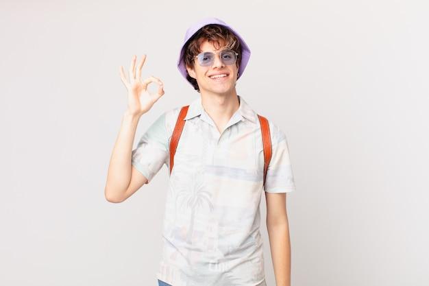 若い旅行者や観光客の男性は幸せを感じ、大丈夫なジェスチャーで承認を示しています