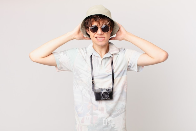 若い旅行者や観光客の男性は、頭に手を置いて、ストレス、不安、または恐怖を感じています