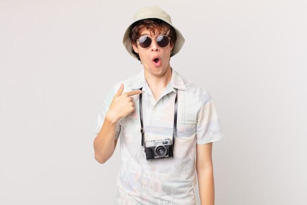 若い旅行者や観光客の男性は、口を大きく開いてショックを受けて驚いて、自分を指しています