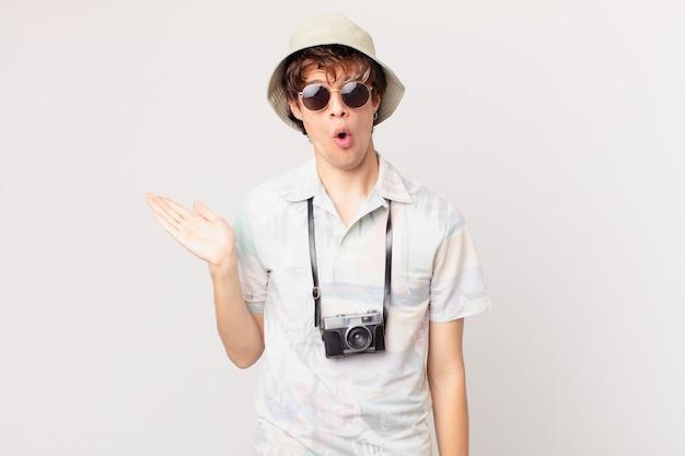 Молодой путешественник или турист, выглядящий удивленным и шокированным, с отвисшей челюстью, держащий предмет