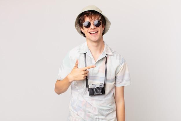 Молодой путешественник или турист, весело улыбаясь, чувствуя себя счастливым и указывая в сторону