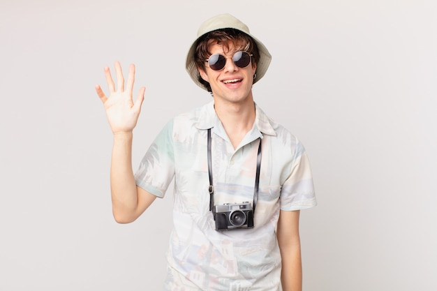 若い旅行者や観光客の男性は幸せに笑って、手を振って、あなたを歓迎し、挨拶します