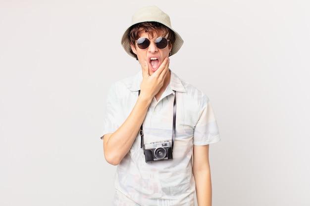 口と目を大きく開いて、あごに手を置く若い旅行者または観光客の男性