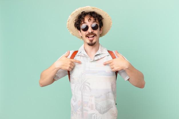 Молодой путешественник турист чувствует себя счастливым и указывая на себя с возбуждением