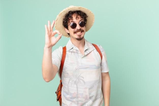 若い旅行者の観光客は幸せを感じ、大丈夫なジェスチャーで承認を示しています