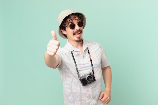 Молодой путешественник-турист чувствует гордость, позитивно улыбается и показывает палец вверх