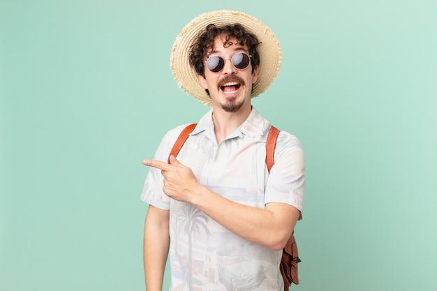 Молодой путешественник-турист выглядит взволнованным и удивленным, указывая в сторону