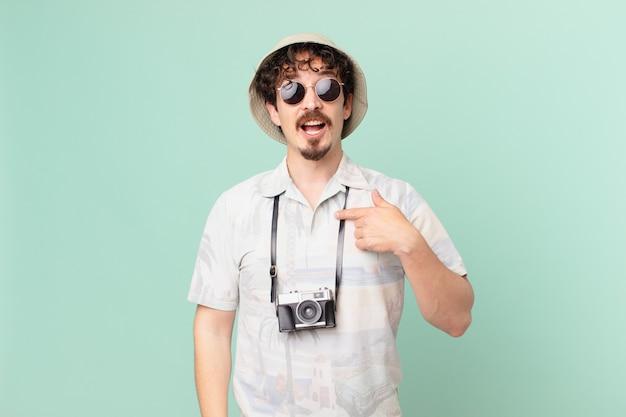 若い旅行者の観光客は、口を大きく開いてショックを受けて驚いて、自分を指しています