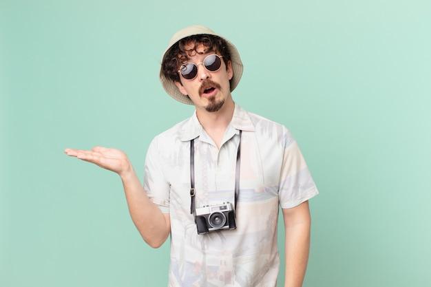 Молодой путешественник-турист выглядит удивленным и шокированным, с отвисшей челюстью, держащим предмет