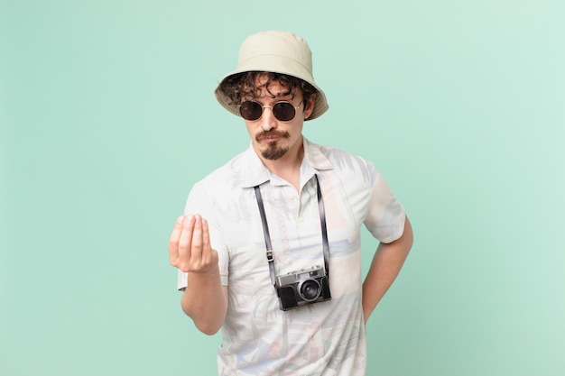 Young traveller tourist making capice or money gesture, telling you to pay