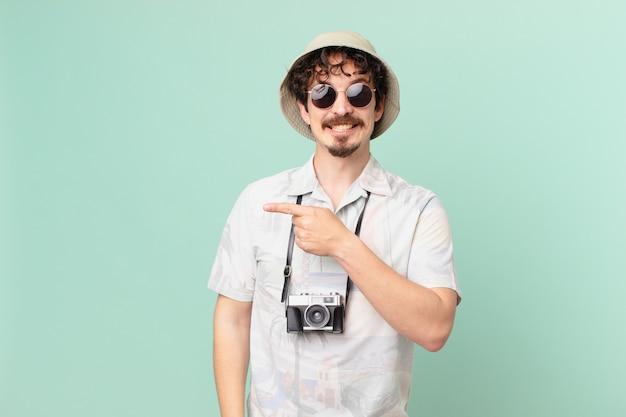 Молодой путешественник-турист весело улыбается, чувствует себя счастливым и указывает в сторону