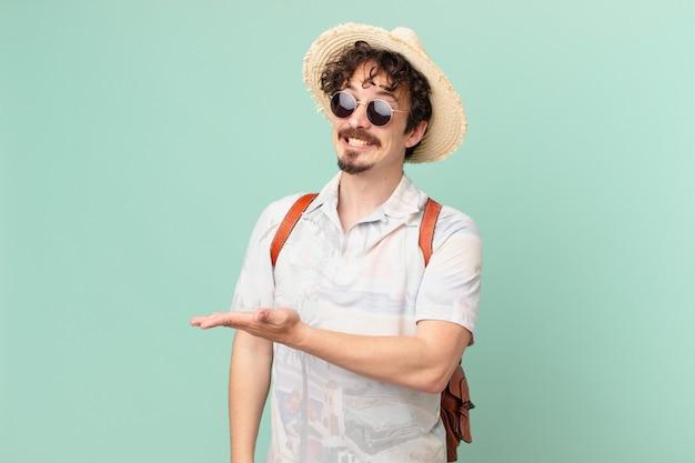 Молодой путешественник-турист весело улыбается, чувствует себя счастливым и демонстрирует концепцию