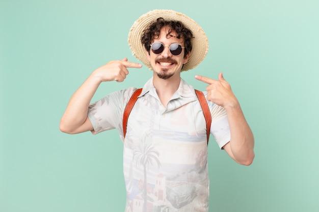 Молодой путешественник-турист, уверенно улыбаясь, указывая на собственную широкую улыбку