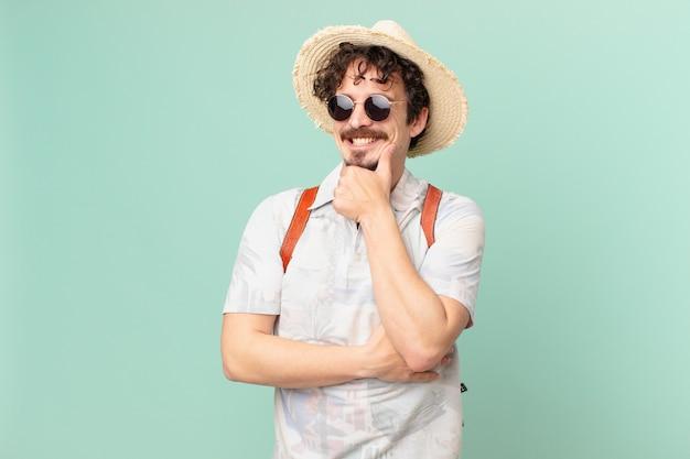 あごに手を添えて幸せで自信に満ちた表情で笑っている若い旅行者の観光客