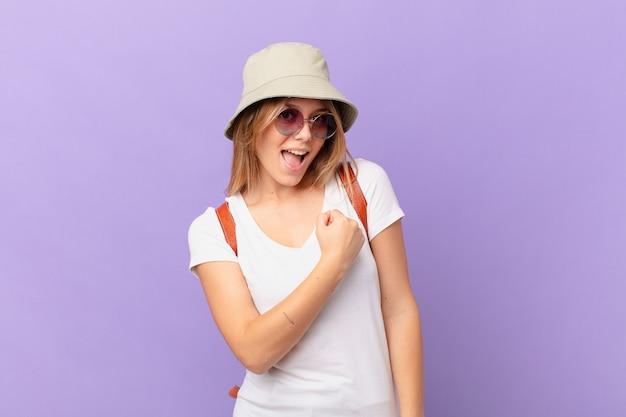 幸せを感じ、挑戦に直面している、または祝っている若い旅行者の観光客の女性