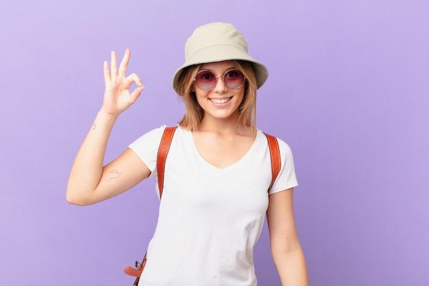 幸せを感じて、大丈夫なジェスチャーで承認を示す若い旅行者の観光客の女性