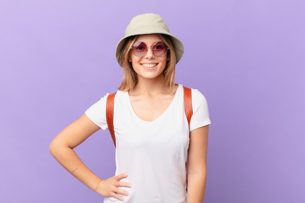 腰に手を当てて幸せに笑って自信を持って若い旅行者観光客の女性