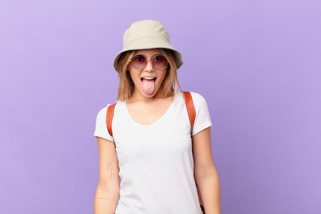 陽気で反抗的な態度、冗談を言ったり、舌を突き出している若い旅行者の観光客の女性