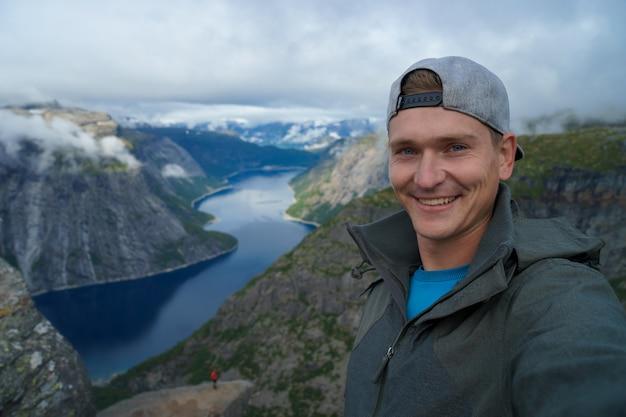 Молодой путешественник в кепке и теплом пальто, делающий селфи на вершине с красивым фьордом на фоне в норвегии.