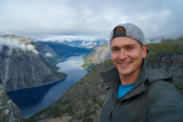 Young traveller wearing cap and warm coat taking selfie on the top with beautiful fjord on surface in norway
