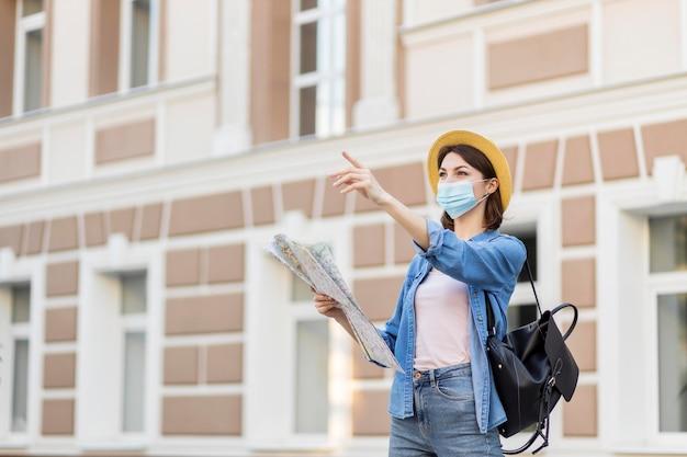 帽子とフェイスマスクを持つ若い旅行者