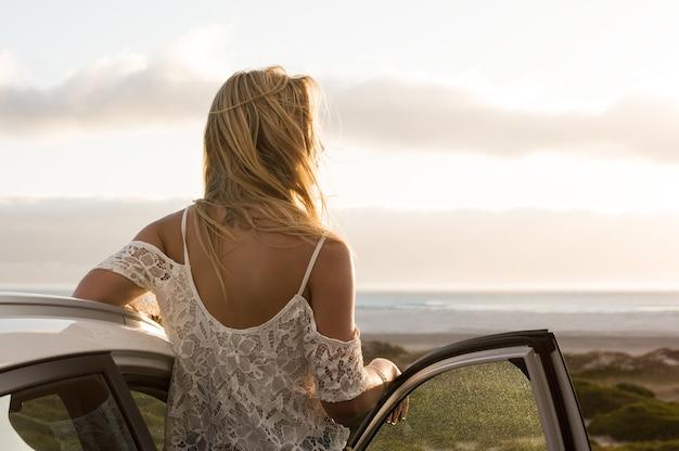 車の外に立って夕日を楽しむ若い旅行者の女性