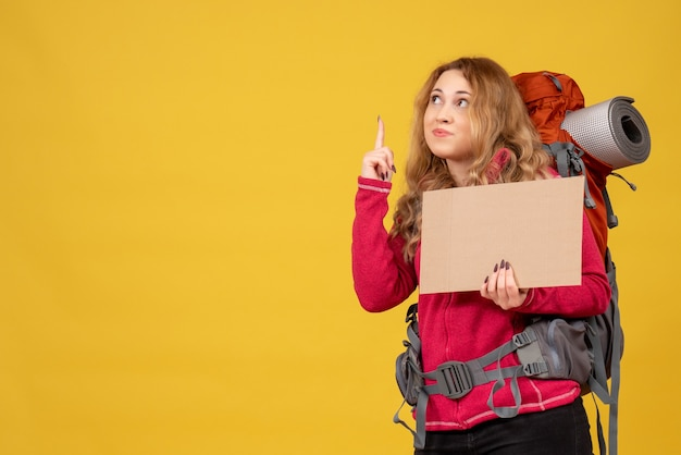 Young travelling girl collecting her luggage showing free space for writing and pointing up