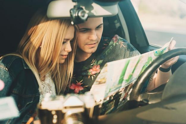 운전석에 앉아있는 사람이 개최하는 도로지도를주의 깊게보고 여름 옷을 입은 자동차 커플 여행 젊은