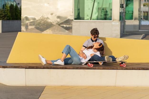 젊은 트렌디한 커플 행복한 껴안고 이야기 롱보드에 앉아 도시 도시 공원에서 야외에서 여름을 즐긴다