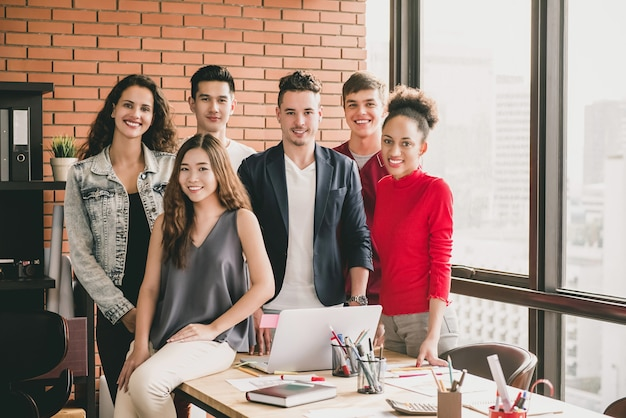 Young trendy diverse smiling millennial team in casual clothes around office table