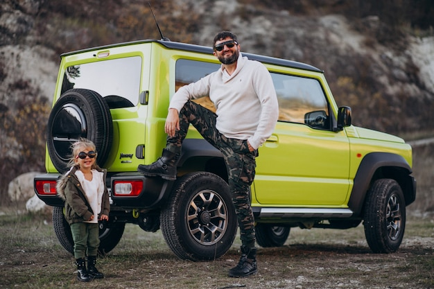 Young trendy father with his little daughter having fun by the car