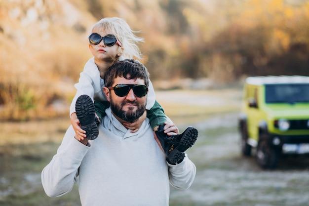 肩の上に座っている彼の小さな娘と若いトレンディな父