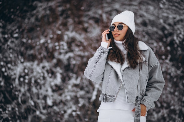 Young trendy girl in a winter park using phone