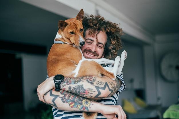 Молодой модный хипстер с татуировками сумасшедших вьющихся волос обнимает своего маленького лучшего друга